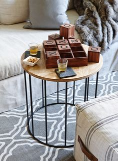 A soft ottoman pulled up to a coffee table creates a cosy spot for playing cards and old-fashioned games like tic-tac-toe. Wooden tic-tac-toe set, $32.97; faux-fur throw, $44.97; french linen pouf, $59.97; solid wood and wire-base table, $99.97; slate coaster set, $11.97. Shop hometrends™ now at www.walmart.ca/hometrends | #walmart #hometrends