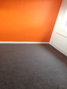 Orange feature wall and grey carpet