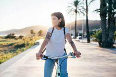 Attractive hipster millennial woman or teenager in blue american denim and simple white tshirt rides bicycle on sunset promenade next to beach, authentic tattoos — Kup to zdjęcie bez tantiem i przeszukaj podobne obrazy w serwisie Adobe Stock