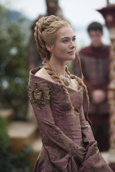 """Cersei continued to stick to her wine color palette and aggressive necklaces. However, since she is the mother-of-the-groom and former Queen Regent, Alexander said they gave her a 'do befitting her station. """"We made a massive hairpiece in the back done up like a circle,"""" he said. They started with a small bun, and kept adding braids and """"ropes"""" of hair."""