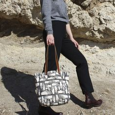 """A sturdy natural canvas tote bag with a hand printed block design. Dimensions: Measures 12.5"""" x 16"""" x 4.75"""". Details: Canvas or Denim. Brown or Black leather straps with a 12"""" drop. Includes interior"""