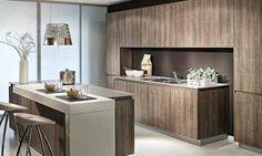 Cuisine moderne en bois. #déco Cuisine sans poignées avec îlot et coin repas moderne. L'évier est éclairé par un pont de meubles semi-encastrés. #design