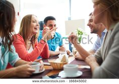 Portrait of happy teenage friends sitting and chatting in cafe