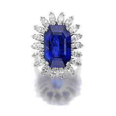 A Ceylon sapphire and diamond ring set with a14.40 carat cut-cornered rectangular-step cut diamond, within a marquise-cut diamond surround, mounted in platinum