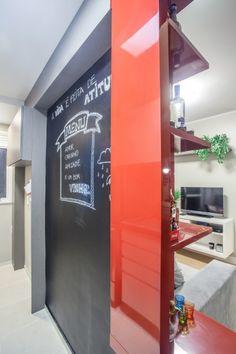 Vista de dentro da cozinha para a sala, mostrando a parede com quadro negro e ao fundo na área de serviço armário aéreo para material de limpeza e na parte de baixo ganchos para vassoura, rodo e panos.