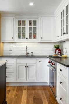 Traditional Kitchen with Farmhouse Flair Cabinetry: WoodMode: BrokHaven Cabinets with Nordic White paint and Matte Twilight finish Kitchen Black Counter, Black Kitchen Countertops, Backsplash For White Cabinets, White Kitchen Cabinets, Kitchen Redo, Home Decor Kitchen, Kitchen Interior, Home Kitchens, Kitchen Remodel