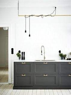 This masculine kitchen features some industrial elements, like pipe and cord lighting with elegant touches in the white tiling and grey cabinets
