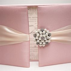 Email  Print          8     Instead of a simple paper suite, dress your wedding invitations up in a satin box with a pearl and crystal brooch clasp. Guests get a surprise inside - it's like unwrapping