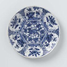 Bord van blauw en wit Delfts aardewerk, versierd met planten en vogels en een grommende wolf of vos in het midden -