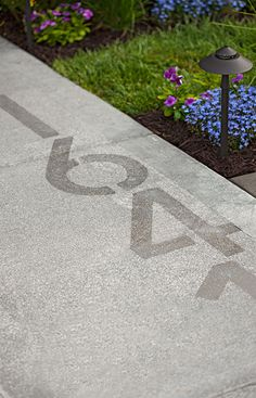 For a new approach to house numbers, apply Rustoleum's NeverWet to your sidewalk. When dry, the house numbers are subtle, but they really stand out when coated with rain.