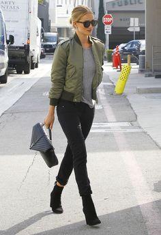 Rosie Huntington-Whiteley, cazadora verde con una camiseta gris básica, pantalones, pitillo, botines y bolso de Saint Laurent, estos tres últimos en negro.