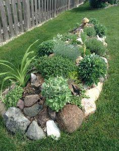jardin de rocaille de taille riquiqui avec des grosses pierres, graminées, plantes couvre-sol et gazon