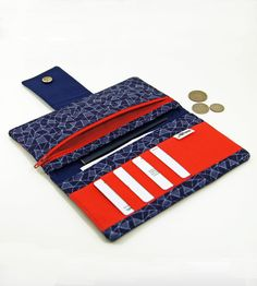"Geometric Passport Wallet (by Minnebites) (2/3) - This handmade wallet is made with geometric patterned cobalt fabric with a bright, poppy red trim and interior. Room for a passport, bills, receipts, up to 8 credit cards (in 4 slots total). There is a snap closure and an interior zippered pocket. Measurements: Zipper opening is 7"", wallet is approximately 8"" x 4"" when closed."