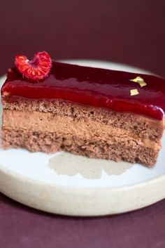 Angela's stunning chocolate framboisier recipe sees layers of chocolate sponge and mousse topped with a rich raspberry glaze.