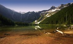 Avalanche Lake, in Glacier National Park, Montana, at sunrise. In summer, the snow melt results in giant waterfalls that tumble over the sheer mountain cliffs. Yellowstone National Park, National Parks, Snow Melt, Sunrise Lake, Yosemite Falls, Rocky Mountains, Waterfalls, Montana, Dawn