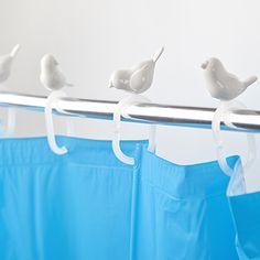 Divertidos ganchos para la cortina de ducha con unos pájaros posados. En color blanco.  La cortina de ducha es uno de los elementos más personalizables del baño, pudiendo elegir su color, diseño o t...