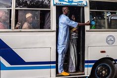 """Beautiful Boubou Friday: A man in a blue boubou and yellow shoes rides a Tata bus during the morning commute in Dakar Sénegal."