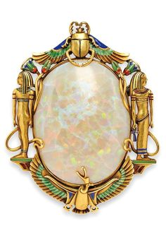Egyptian Revival. 14kt Gold, Opal, and Enamel Brooch, Marcus & Co., the opal framed by ancient Egyptian motifs with enamel accents.