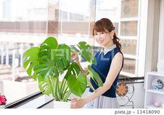 観葉植物をさわる笑顔の若い女性