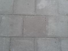 Een betonnen grondlaag die niet zo symmetrisch tegenover elkaar staan. Ze worden van elkaar afgescheiden door zwart/grijze strepen
