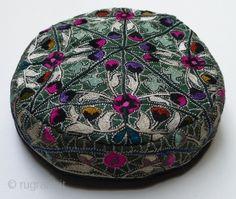 "Tashkent Hat. Uzbekistan, circa 1930's. 21.5"" circumference x 7"" diameter x 1.5"" high. Silk embroidery on dark green silk; cotton muslin lin..."