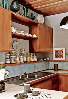Pale blue subway tiles form a playful splashback in the kitchen of this mid-century style home.
