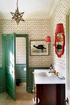 In a ground-level bathroom, wallpaper brings joy and inspiration to the space while a bright red mirror brings it all together. #bathroom #bathroomideas #inspo #ideas #decor #mirrors #marble #sink #wallpaper #lightfixture #brass #crownmolding #art Guest Bathrooms, Downstairs Bathroom, Bathroom Ideas, English Country Style, Georgian Homes, Interior Decorating, Interior Design, Decorating Ideas, Bathroom Wallpaper