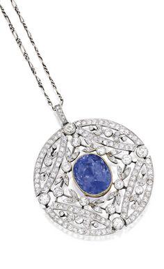 Platinum, Gold, Sapphire and Diamond Pendant. Centering an oval-shaped sapphire weighing 13.50 carats, within garland surrounds set with round and old European-cut diamonds weighing approximately 3.70 carats, suspended from a fancy link chain, chain length 14½  inches. Via Sotheby's.