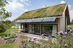 "Sustainability -- This small dwelling utilizes a ""green"" roof, photo-voltaic panels, and what appears to be a small backyard garden to be more sustainable. Green Architecture, Sustainable Architecture, Small Backyard Gardens, Backyard Landscaping, Roof Design, House Design, Eco Buildings, Living Roofs, Earthship"