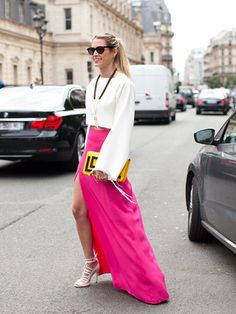 White boxy crop top with frayed sleeves, fuchsia slit maxi, white strappy heels, pendant necklace and graphic yellow/black clutch