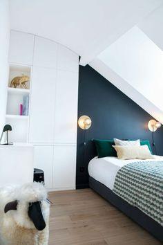 idée déco chambre adulte sous les combles, en bleu canard sur le mur du lit, grande armoire blanche, avec des étagères hautes, revêtement du sol en marron