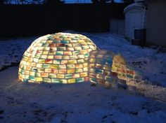 """collecting hundreds upon hundreds of milk cartons and filling the empty shells with colored water then frozen, the bricks for the igloo were formed. One by one, the cartons were peeled away to reveal the gorgeous, glowing ice building material for the outdoor """"shed."""" Bonding the varying bricks with """"snowcrete"""" (snow and water) was another part of the system"""