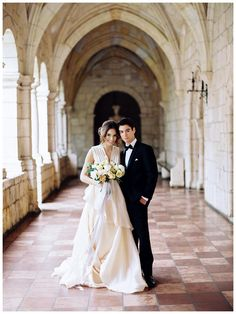 Bride and groom at The Ancient Spanish Monastery in North Miami Beach, FL. Blush wedding dress by Chaviano Couture, classic tuxedo from The TUXXMAN, bridal bouquet by Elleson Events. Photographed by Simply Sarah Photography.
