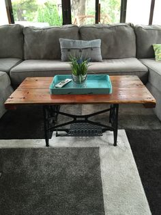 Coffee table made from barn door and antique sewing machine base