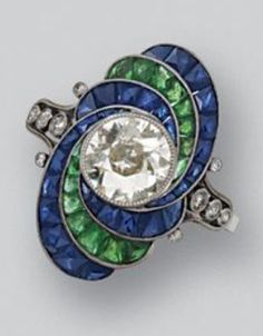 An Art Deco diamond, sapphire and emerald ring, circa 1925. Set with an old European-cut diamond weighing approximately 1.00 carat within an oval frame decorated with swirls of French calibré-cut emeralds and sapphires, the shoulders accented with small old European-cut diamonds, mounted in platinum. #ArtDeco #ring