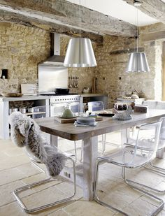 Modern rustic kitchen: Old stone walls, stainless steel stove and backsplash, rustic wood table, lucite and chrome dining chairs.  Vintage House in Dordogne, France | Home Adore