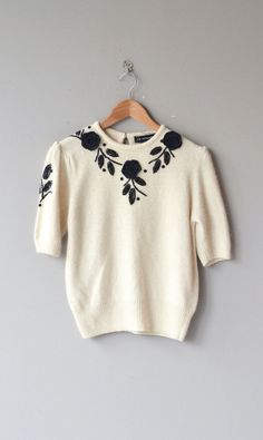Vintage 1980s ultra soft ivory silk & angora sweater with short sleeves and black beaded and floral applique along the neckline. Keyhole closure at