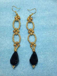 Beautiful earrings with gold seed beads, pearls and a black crystal drop.