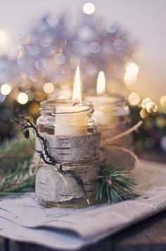 A rustic display of holiday candles in mason jars decorated with birch bark & twine.