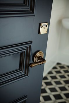 "Brass hardware stands out against a dark door… the ""occupied"" lock on the bathroom door is pretty AND practical."