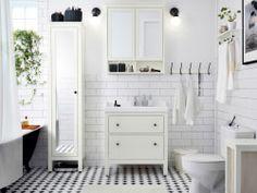 Uma casa de banho branca com azulejos, armário para lavatório e armário alto com porta espelhada. Combinados com um lavatório branco e um armário de parede com portas espelhadas.