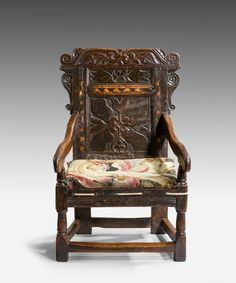A Jacobean carved oak wainscot armchair. A beautifully carved Seventeenth Century oak wainscot armchair; the original cresting carved with scrolling leaves above a back inlaid with a broad banding of light and dark holly and the main panel is carved with a stylised tulip flower; having a later rope seat and raised on turned legs united by beautifully worn stretchers.:
