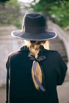 jolie tresse sur cheveux blondes avec un mignon ruban noir, coiffure d'été femme