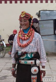 Gannan Tibetan woman happily poses wearing coral, amber and silver ornaments