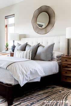 A contemporary bedroom with a mirror above the tufted headboard. We love the personality driven nightstands that you can buy on our website. Color enters this clean space with silver blue euros and a funky animal print rug | Modern Glass House designed by Alice Lane