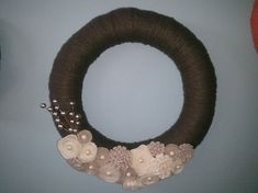 Chocolate yarn wreath with ivory flowers and bronze twig garnishments. It is a 14 straw wreath wrapped in brown yarn.