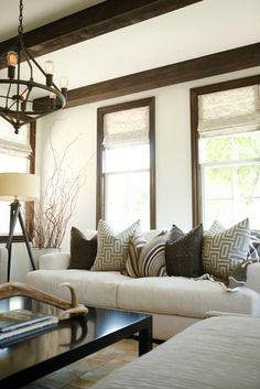 Cozy and neutral living room with white walls, exposed wood beams, and wood trim.