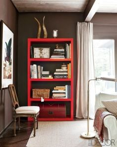red parson bookcase against dark gray wall, masculine bedroom, how to style a bookcase