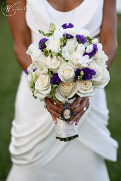 Bouquet of white English roses and purple statice accented with a purple and white cameo brooch.