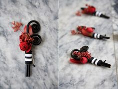 Love this:   Groomsmen boutonnieres are designed with air brushed black fern curls, a red ranunculus bud, red seeded eucalyptus, and red leucadendrom bound in black & white stripe ribbon.